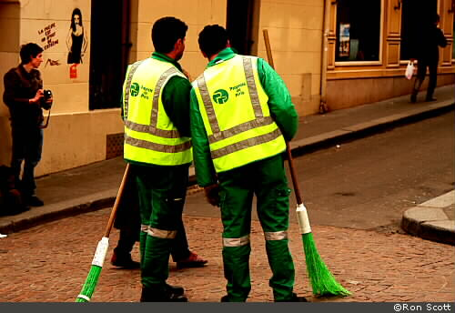 Street cleaners in green uniforms with green brooms in the rue